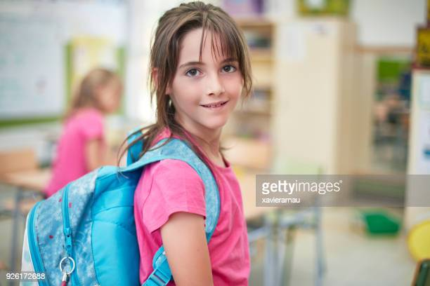 portrait of schoolgirl with backpack in classroom - pink colour stock pictures, royalty-free photos & images