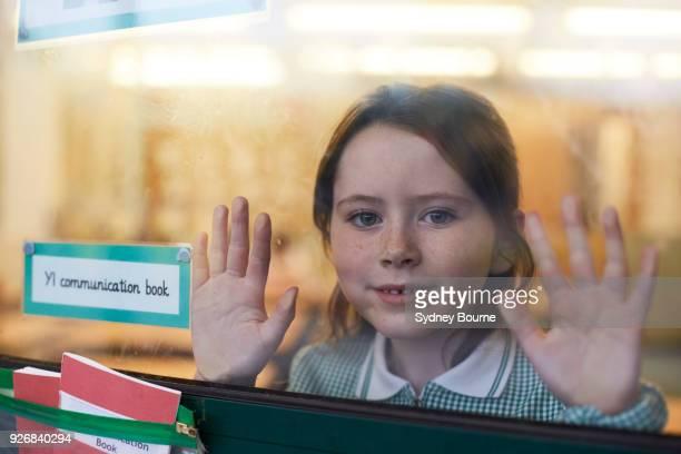 portrait of schoolgirl with hands on classroom window at primary school - front view bildbanksfoton och bilder