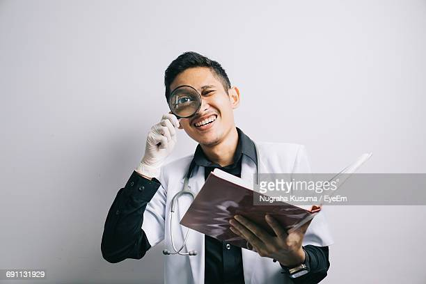 Portrait Of Scientist Magnifying Glass Over White Background