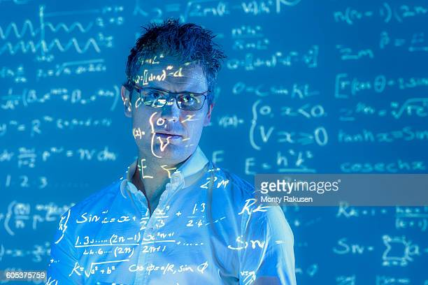 Portrait of scientist with projected mathematical data