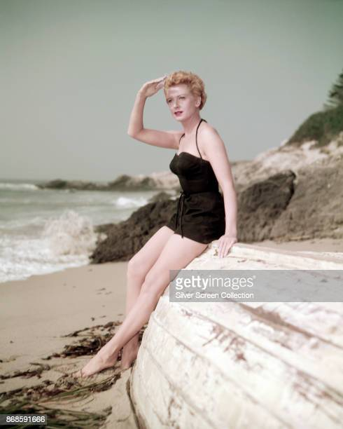 Portrait of Scottish actress Deborah Kerr in a black swimsuit as she leans against an overturned boat on a beach 1940s or 1950s