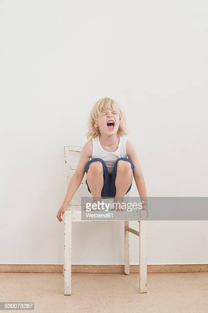 Portrait of screaming little boy crounching on a chair