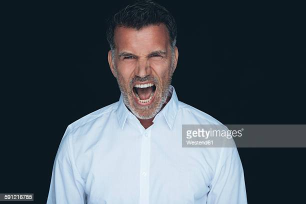 portrait of screaming man white shirt in front of black background - wit hemd stockfoto's en -beelden