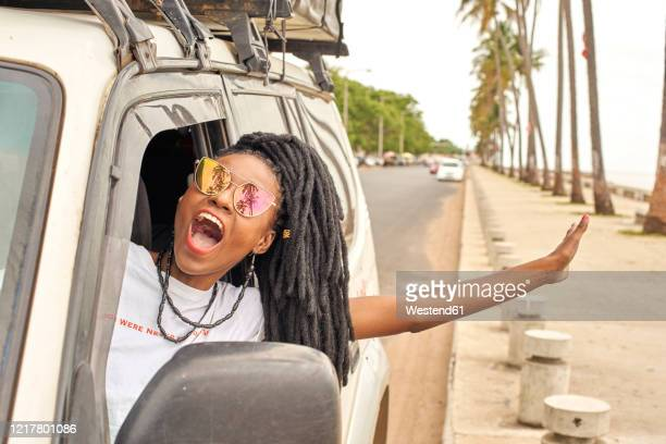 portrait of screaming woman with dreadlocks leaning out of car window, maputo, mozambique - mozambique stock pictures, royalty-free photos & images