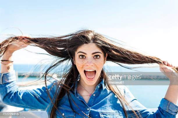 Portrait of screaming young woman pulling her hair