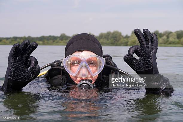 portrait of scuba diver with ok sign in lake - aqualung diving equipment stock pictures, royalty-free photos & images