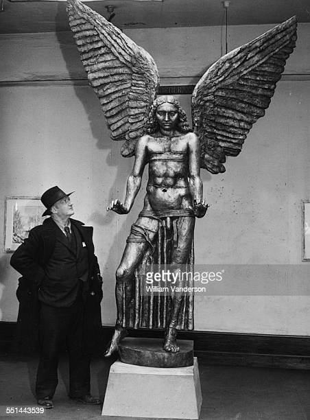 Portrait of sculptor Jacob Epstein with his bronze statue of 'Lucifer' which is part of an exhibition at Leicester Galleries London November 14th 1945