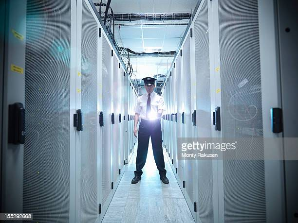 Portrait of security guard shining torch in computer server room