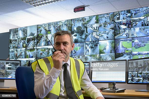 Portrait of security guard using walkie talkie in security control room with video wall