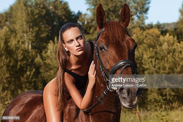 Portrait Of Seductive Woman Riding Brown Horse On Field