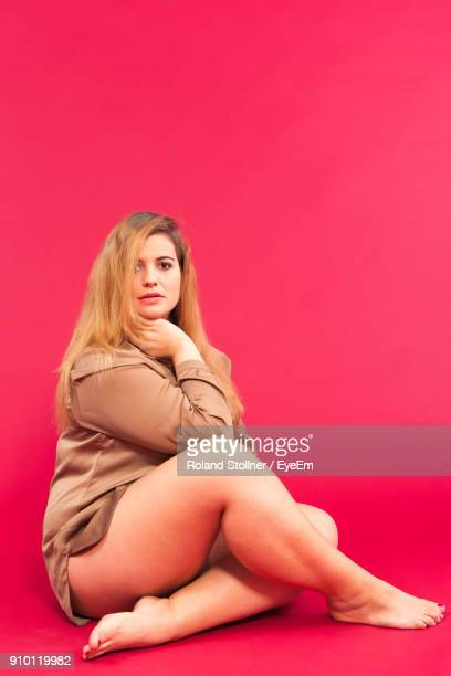 portrait of seductive woman sitting against maroon background - big fat white women stockfoto's en -beelden
