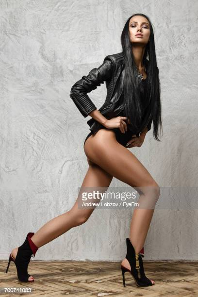 portrait of seductive woman wearing high heels while posing against wall - black sexual stock photos and pictures