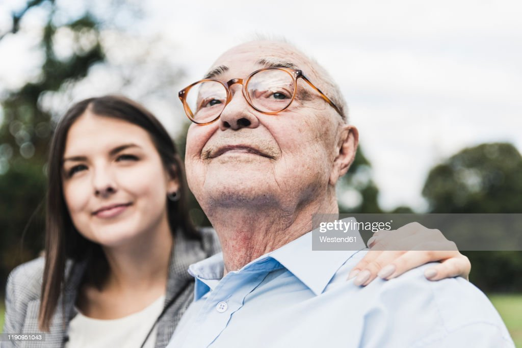 Portrait of self-confident senior man with granddaughter in the background : Stock Photo