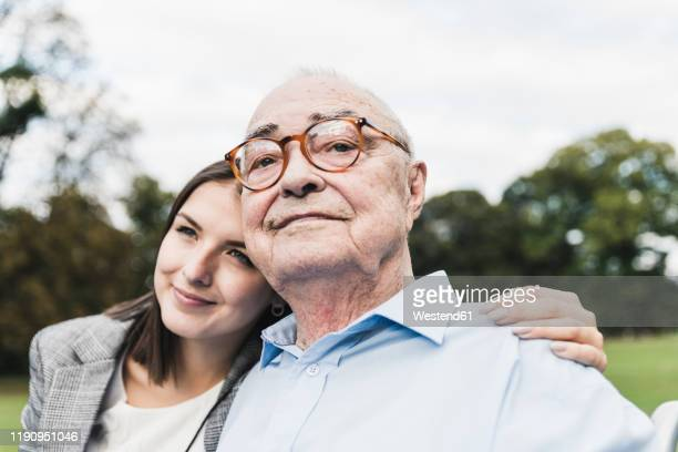 portrait of self-confident senior man with his granddaughter in a park - doing a favor stock pictures, royalty-free photos & images