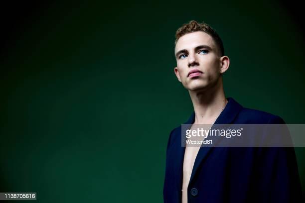 portrait of self-confident young man wearing blue sports jacket in studio - ijdel stockfoto's en -beelden