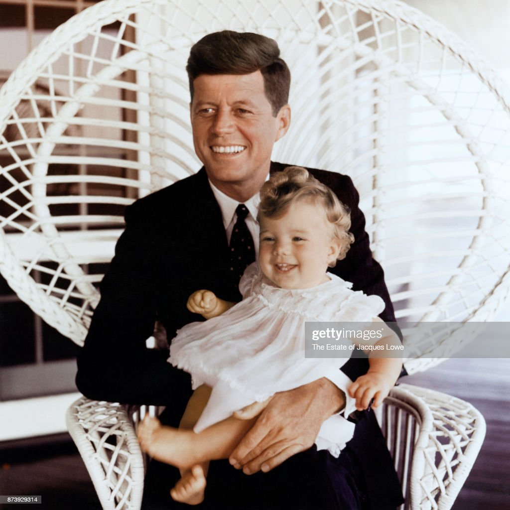 Portrait of Senator (and future US President) John F Kennedy (1917 - 1963) as he poses with his daughter Caroline in his lap, Hyannis Port, Massachusetts, Summer 1958. The photo was taken during a formal portrait shoot and was the first time the photographer had met the Kennedys.