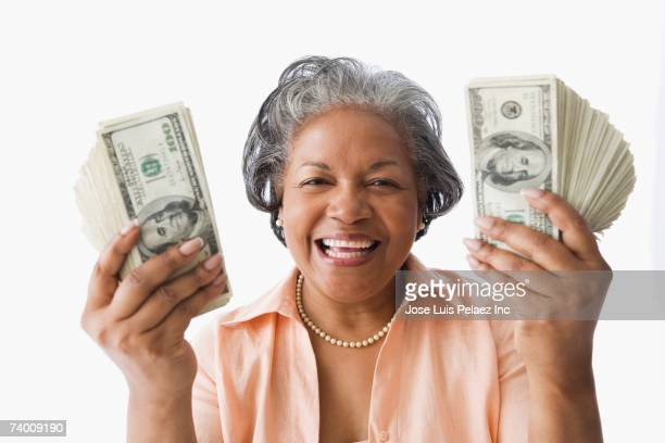 Portrait of senior African woman holding money