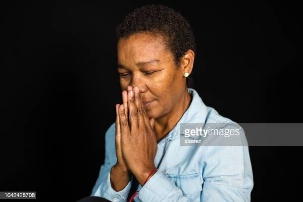 portrait of senior african woman praying - women prayer stock pictures, royalty-free photos & images