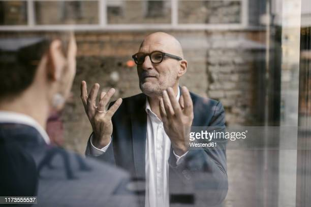 portrait of senior and mid-adult businessman having a meeting - successor stock pictures, royalty-free photos & images