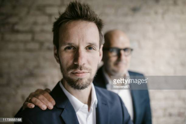 portrait of senior businessman behind and mid-adult businessman - hand auf der schulter stock-fotos und bilder