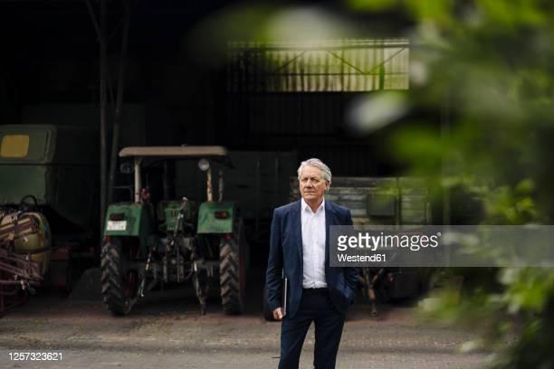 portrait of senior businessman holding laptop on a farm with tractor in barn - unternehmer stock-fotos und bilder