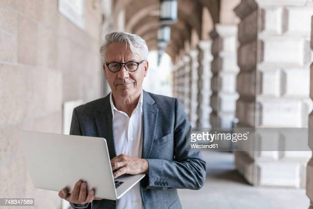 portrait of senior businessman holding laptop - respekt stock-fotos und bilder