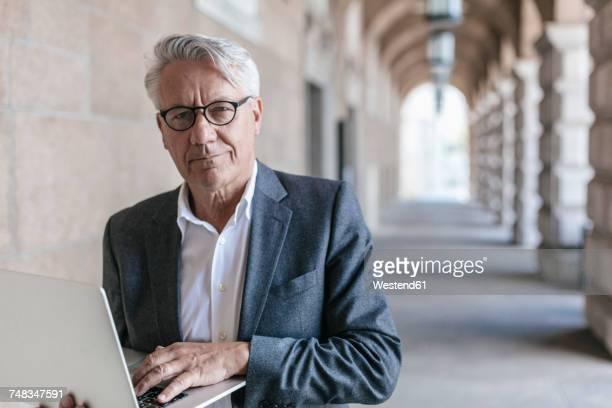 portrait of senior businessman holding laptop - 65 69 ans photos et images de collection