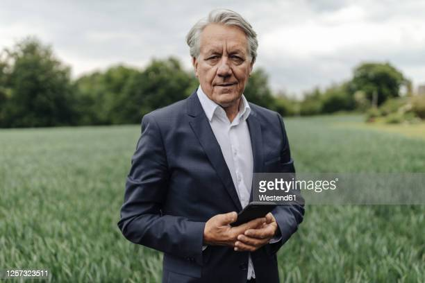 portrait of senior businessman holding smartphone on a field in the countryside - businesswear stock pictures, royalty-free photos & images