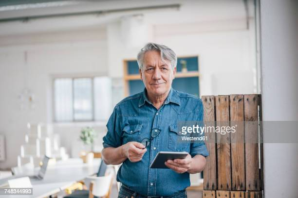 portrait of senior businessman holding tablet in office - senior stock-fotos und bilder