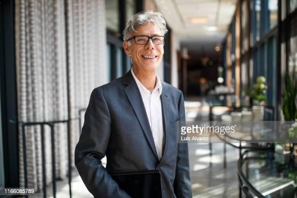 portrait of senior businessman in hotel corridor - businessman stock-fotos und bilder