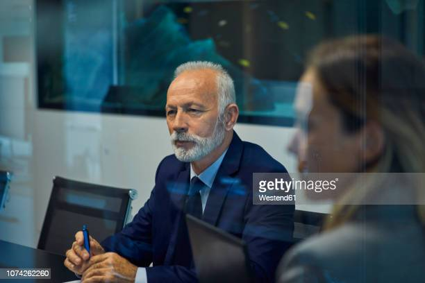 portrait of senior businessman listening in a meeting - formal businesswear stock pictures, royalty-free photos & images