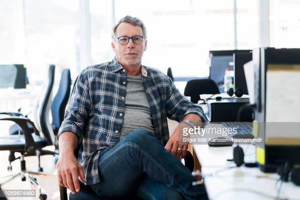 portrait of senior businessman sitting at desk - plaid shirt stock pictures, royalty-free photos & images