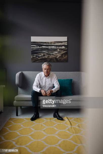 portrait of senior businessman sitting on a couch - one man only stock pictures, royalty-free photos & images
