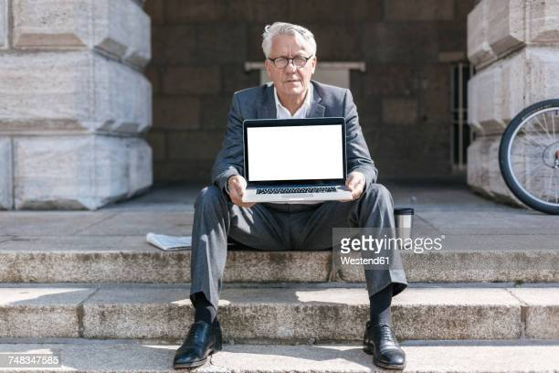 portrait of senior businessman sitting on stairs showing laptop - showing respect stock pictures, royalty-free photos & images