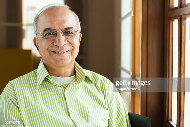 portrait of senior businessman smiling by office window - indian subcontinent ethnicity stock pictures, royalty-free photos & images