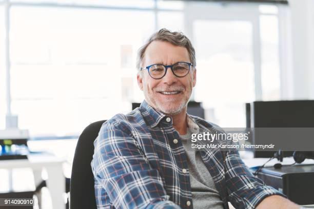 Portret van senior zakenman glimlachend in kantoor