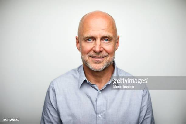 portrait of senior businessman smiling - europese etniciteit stockfoto's en -beelden