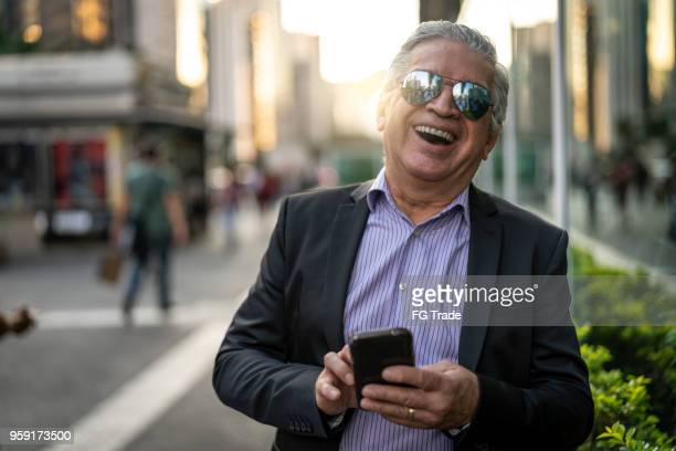 portrait of senior businessman using mobile at city - only senior men stock pictures, royalty-free photos & images