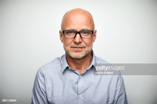 portrait of senior businessman wearing eyeglasses - tête composition photos et images de collection