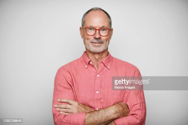 portrait of senior businessman wearing shirt - porträt stock-fotos und bilder