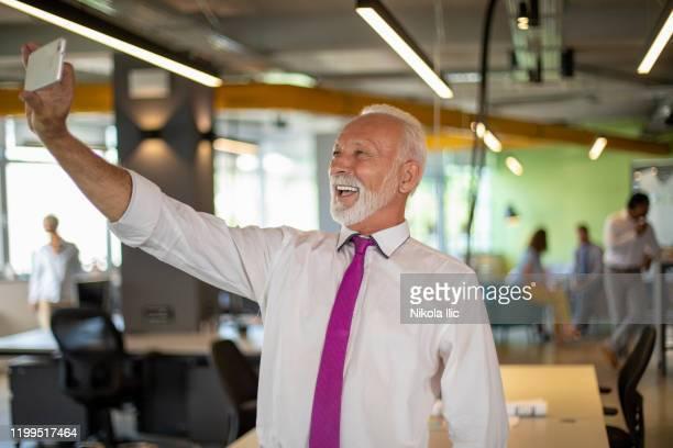 portrait of senior businessman with mobile phone make selfie. - zakelijke kleding stock pictures, royalty-free photos & images