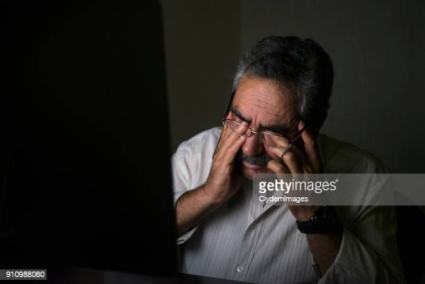 Portrait of senior businessman working late rubbing his eyes in his home office