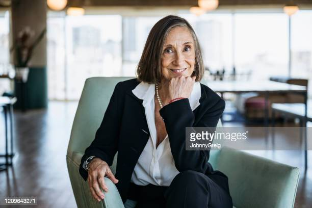 portrait of senior businesswoman seated in comfortable chair - chief executive officer stock pictures, royalty-free photos & images