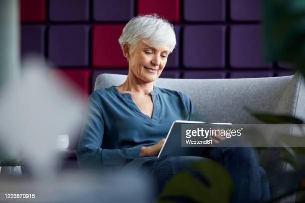 portrait of senior businesswoman sitting on lounge chair using digital tablet - 60 64 jahre stock-fotos und bilder