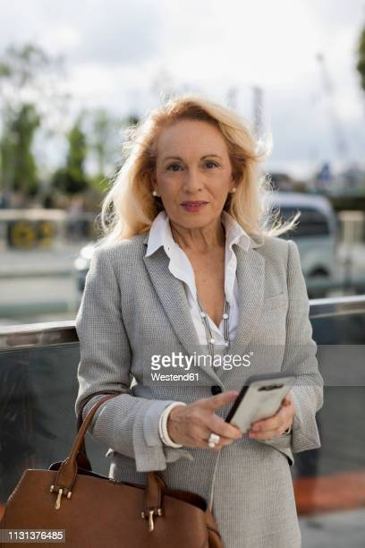 portrait of senior businesswoman with cell phone in the city - gray purse stock pictures, royalty-free photos & images