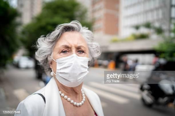 portrait of senior businesswoman with mask - malattia infettiva foto e immagini stock