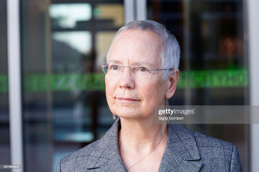 Portrait of senior businesswoman with short grey hair outside hotel entrance : Stock-Foto