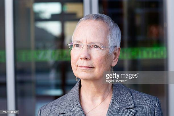 portrait of senior businesswoman with short grey hair outside hotel entrance - sigrid gombert stock pictures, royalty-free photos & images