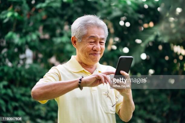 portret van senior chinese man met smartphone - maleisië stockfoto's en -beelden