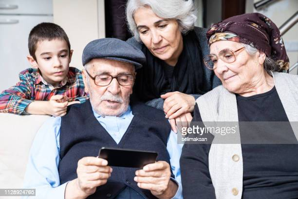Portrait Of Senior Couple And Grandson Using Smartphone